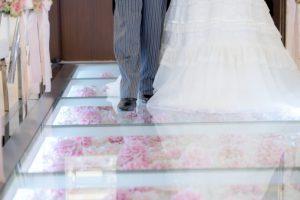 お花のバージンロードを歩く新婦と父