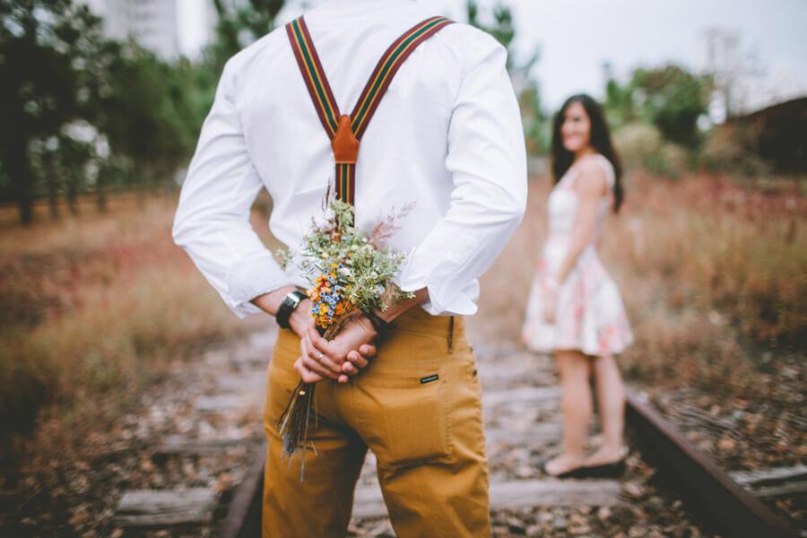花束を持って告白する男性の後ろ姿