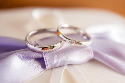 紫リボンのリングピローに乗せられた結婚指輪