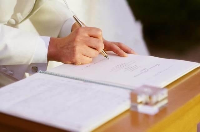 結婚証明書に署名する新郎