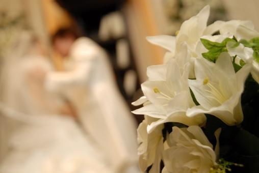 ウエディングキス前の新郎新婦と白い花
