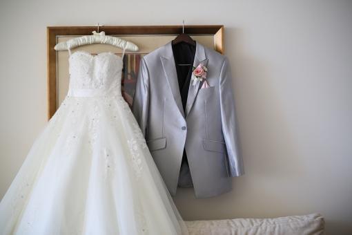 ハンガーに掛けられたウエディングドレスとタキシード