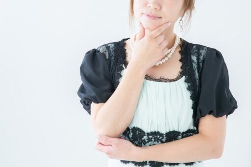 顎に手を当てるドレス姿の女性