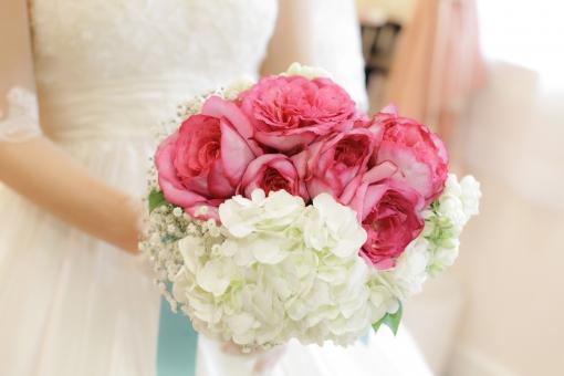 赤がワンポイントのラウンドブーケを持つ花嫁
