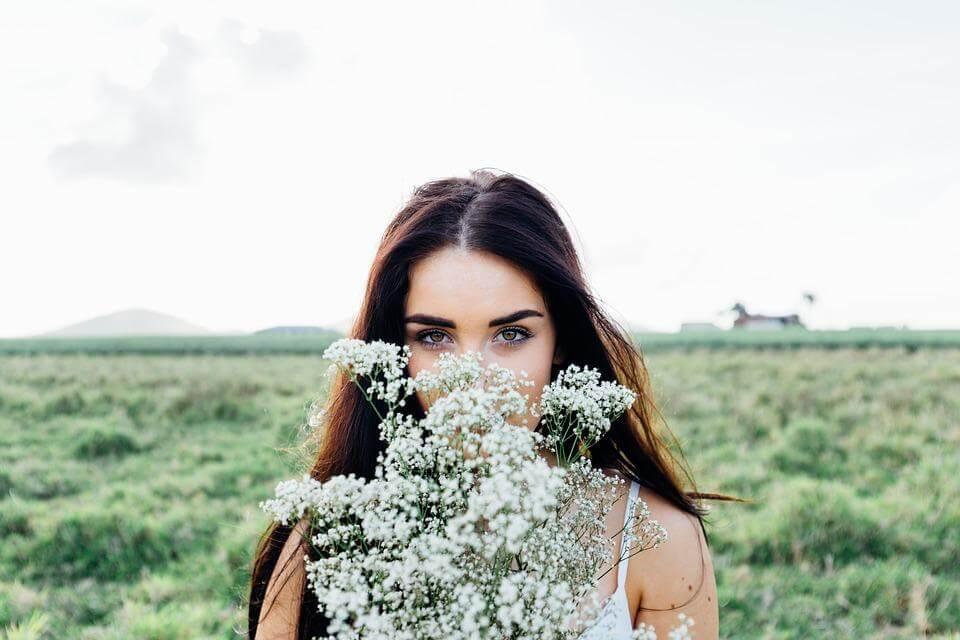 かすみ草を持つ恥ずかしそうな女性