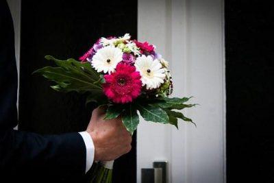 赤のバラと白のガーベラのブーケを持つ男性の手