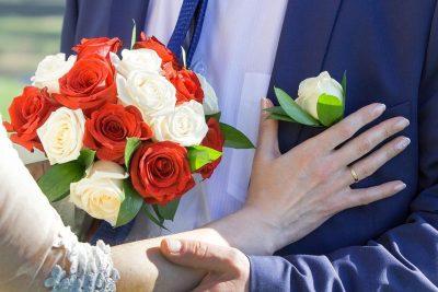 赤白のブーケから、白いバラを新郎の胸ポケットに贈る新婦の手