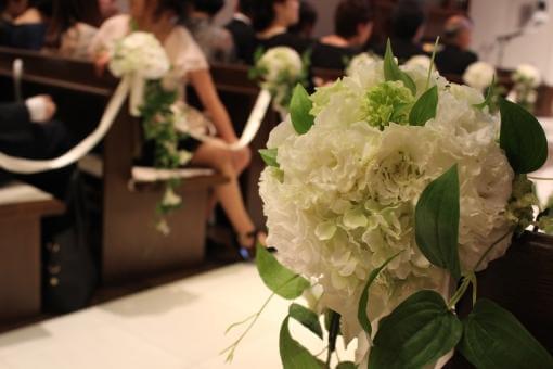 会場装花越しにいる挙式会場内のゲスト