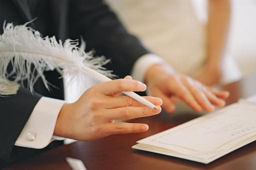 羽ペンを持ち、結婚証明書を書く新郎側立会人代表