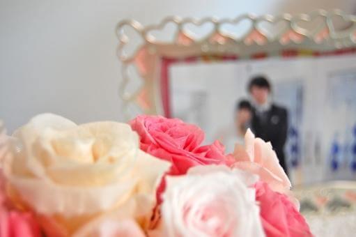 ピンク系バラ越しの新郎新婦の写真
