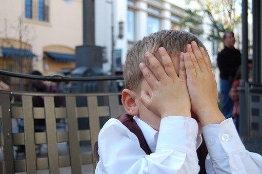 恥ずかしくて手で顔を隠す男の子