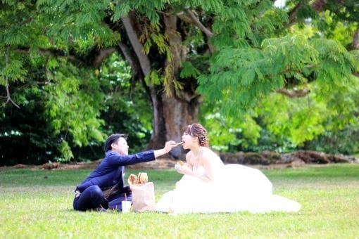 大きな木の前でピクニックする新郎新婦