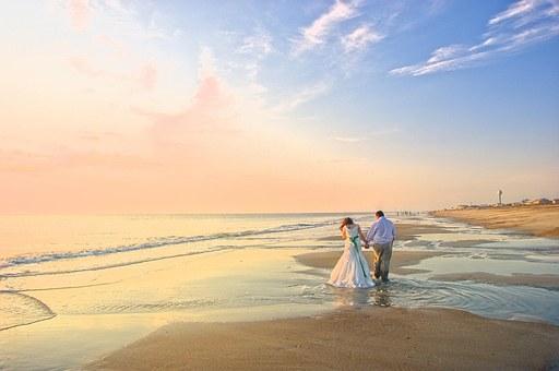夕暮れの海辺を歩く新郎新婦の後ろ姿