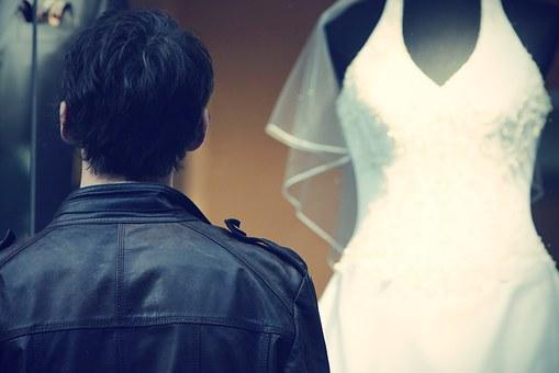 ウエディングドレスを見つめる男性の後ろ姿