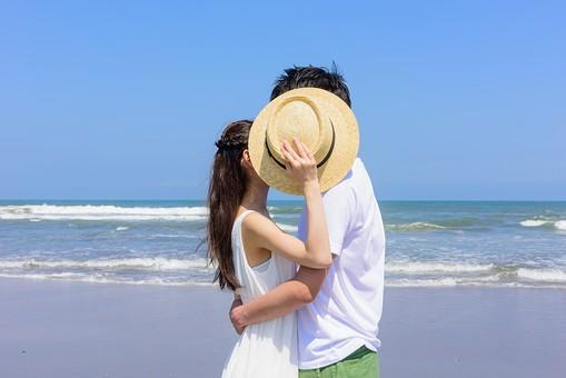 帽子でかくしてキスするカップル