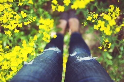 菜の花畑に立つ女性の足元