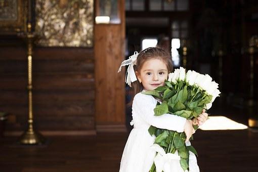 白いバラをたくさん抱える女の子