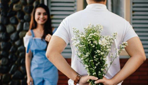 後ろ手に花束を持つ男性